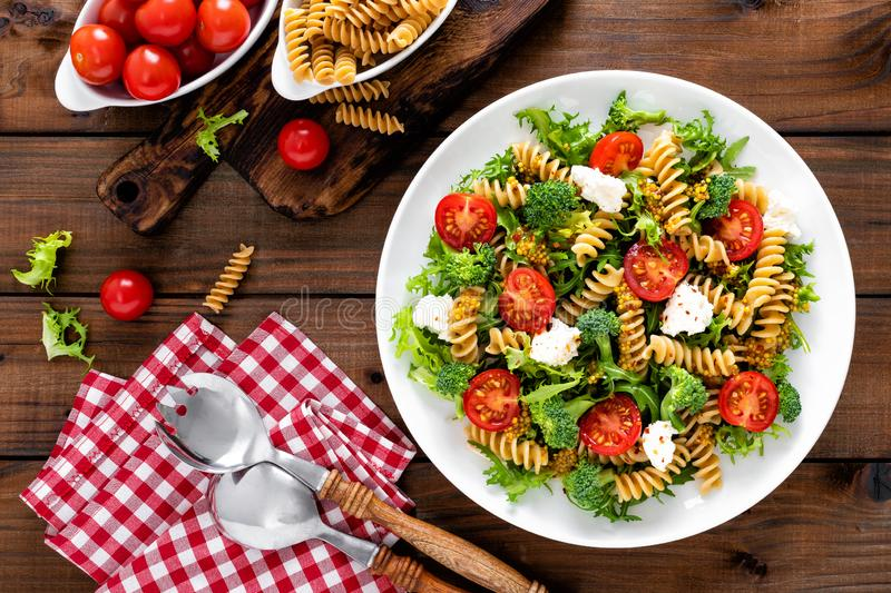 Italian pasta salad with wholegrain fusilli, fresh tomato, cheese, lettuce and broccoli on wooden rustic background. Mediterranean cuisine. Cooking lunch royalty free stock photos