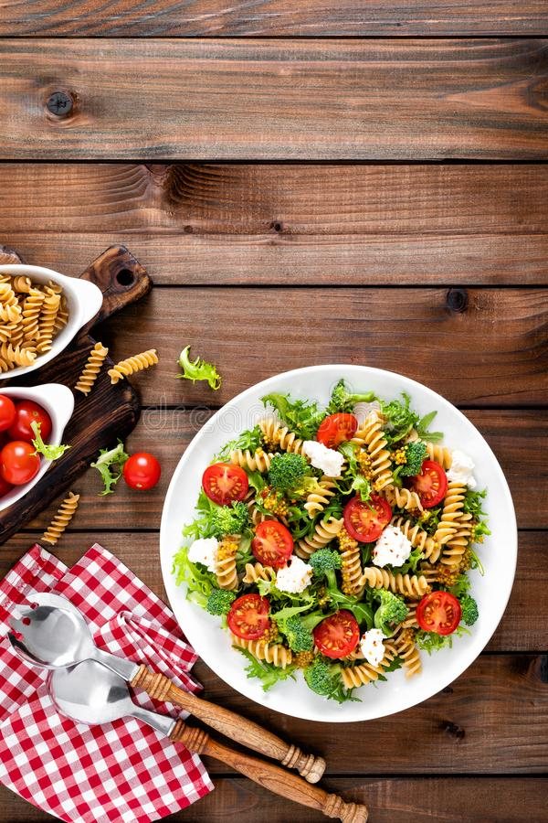 Italian pasta salad with wholegrain fusilli, fresh tomato, cheese, lettuce and broccoli on wooden rustic background. Mediterranean cuisine. Cooking lunch royalty free stock photography
