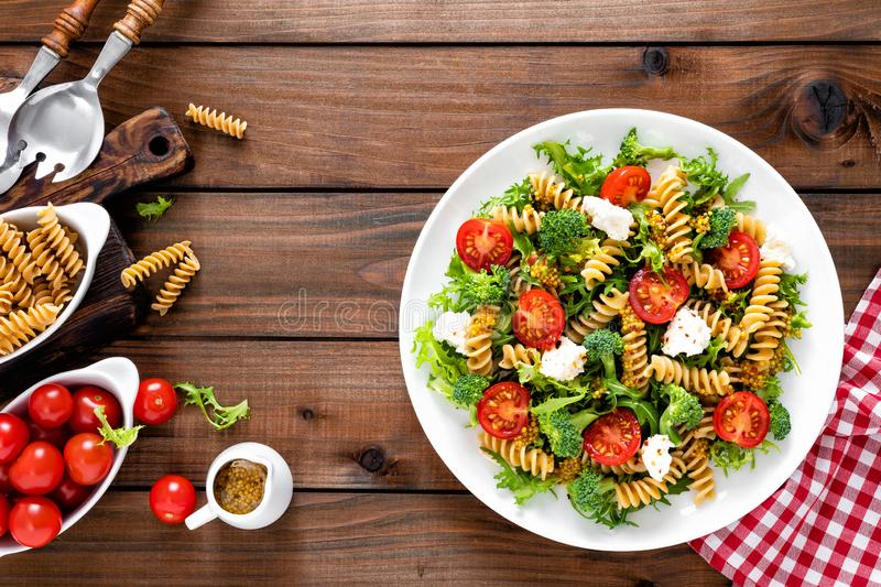 Italian pasta salad with wholegrain fusilli, fresh tomato, cheese, lettuce and broccoli on wooden rustic background. Mediterranean cuisine. Cooking lunch stock images
