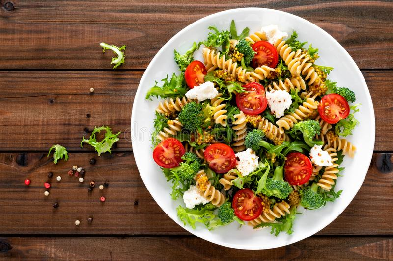 Italian pasta salad with wholegrain fusilli, fresh tomato, cheese, lettuce and broccoli on wooden rustic background. Mediterranean cuisine. Cooking lunch royalty free stock images