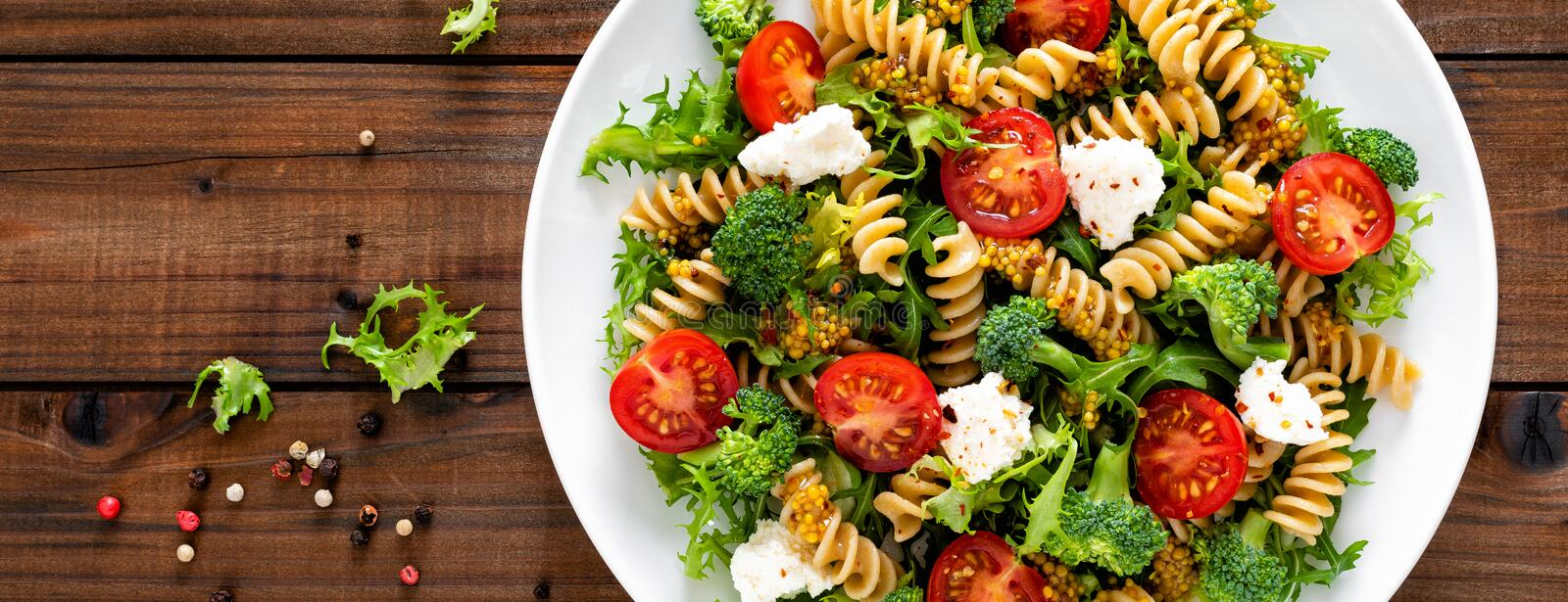 Italian pasta salad with wholegrain fusilli, fresh tomato, cheese, lettuce and broccoli on wooden rustic background. Mediterranean cuisine. Cooking lunch stock photos