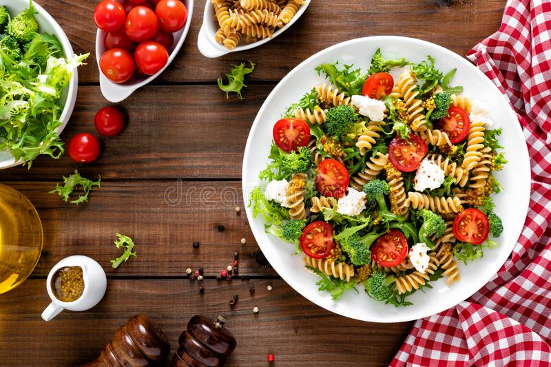 Italian pasta salad with wholegrain fusilli, fresh tomato, cheese, lettuce and broccoli on wooden rustic background. Mediterranean cuisine. Cooking lunch stock photography