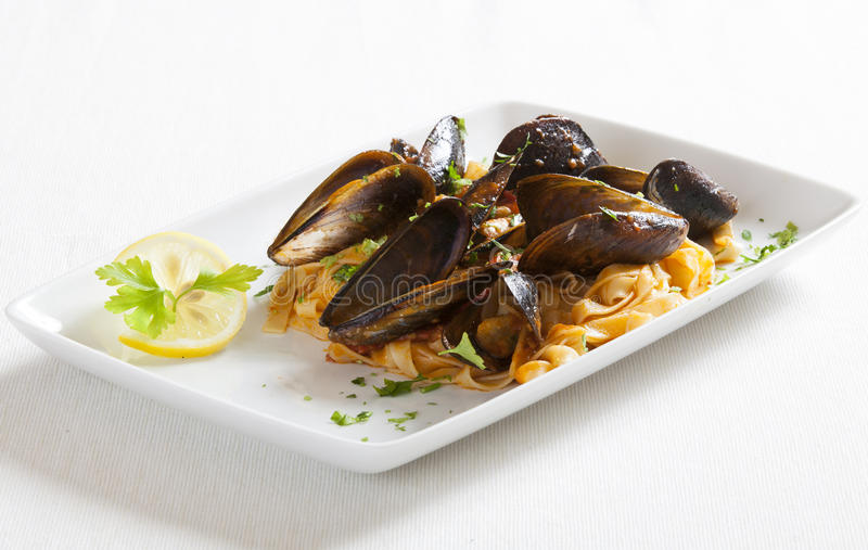 Italian pasta with sea food. Mussels, lemon and tomatoes sauce stock photo