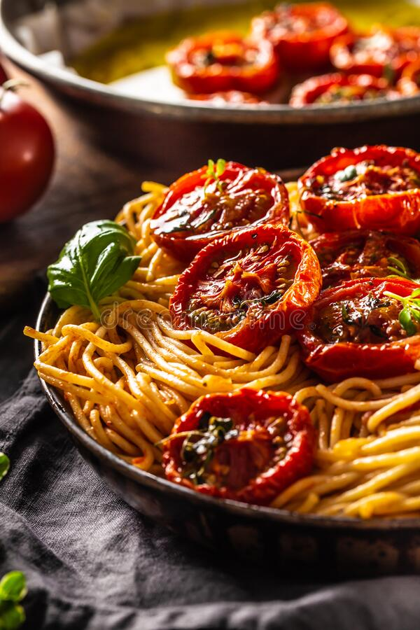 Italian pasta spaghetti with roasted tomatoes basil oregano and thyme stock photos