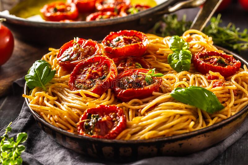 Italian pasta spaghetti with roasted tomatoes basil oregano and thyme royalty free stock photo