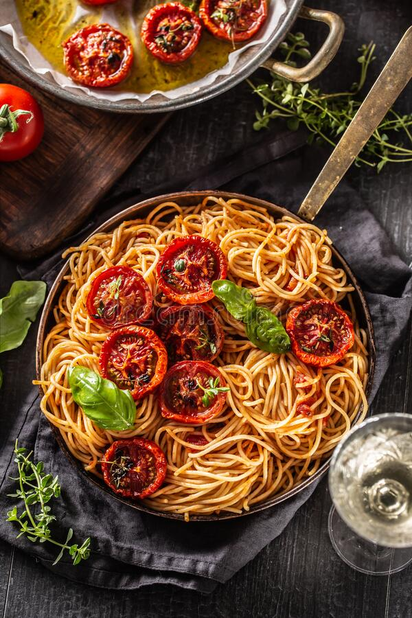 Italian pasta spaghetti with roasted tomatoes basil oregano thyme and white vine royalty free stock photography