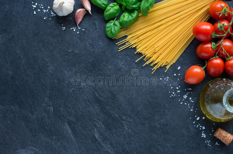 Italian pasta. Spaghetti, tomatoes and others ingrdients for italian pasta on blackboard royalty free stock image