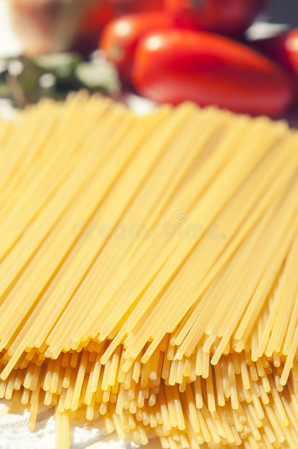 Italian pasta. With tomatoes in the background royalty free stock photos