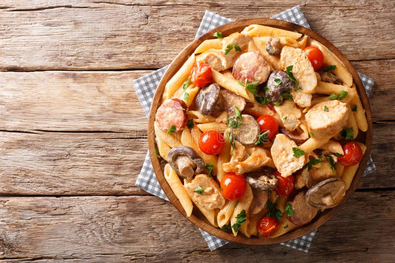 Italian penne pasta with chicken fillet, mushrooms, smoked sausage, cayenne pepper covered with cream cheese sauce close-up on a stock images