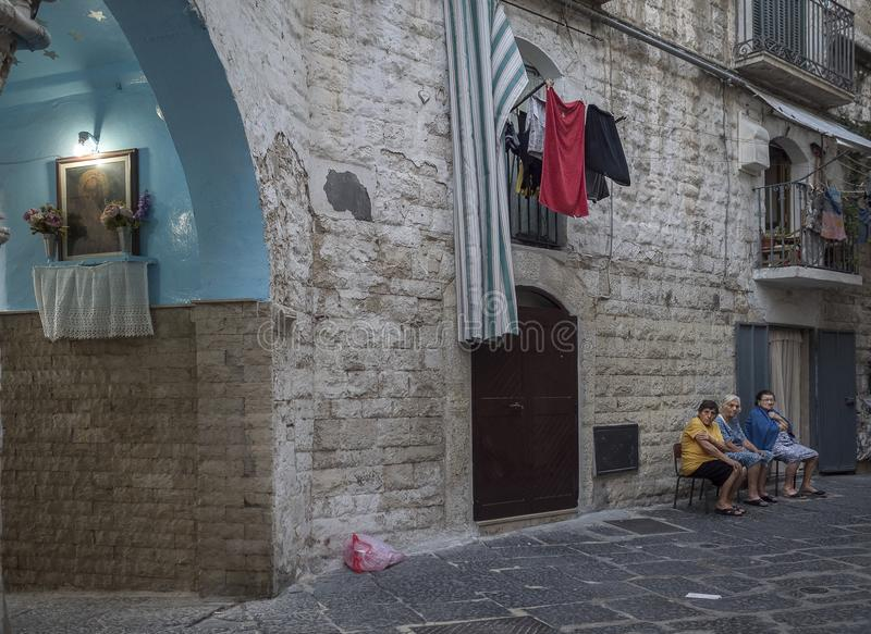 Italian people in the street in south italy. Italian south women in the street are chatting after dinner. windows padre pio laundry stock image