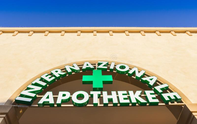 Italian Pharmacy Sign and Shop. Pharmacy sign in German language. Green color teaches stock photography