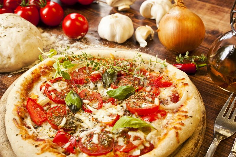 Italian Pizza. Decorated with fresh green herbs stock photo
