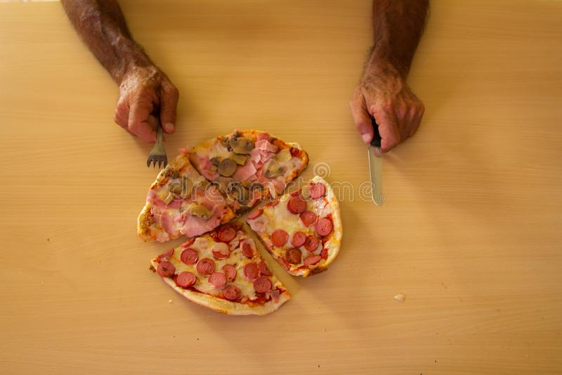 Italian pizza approaching the eater`s hands stock image