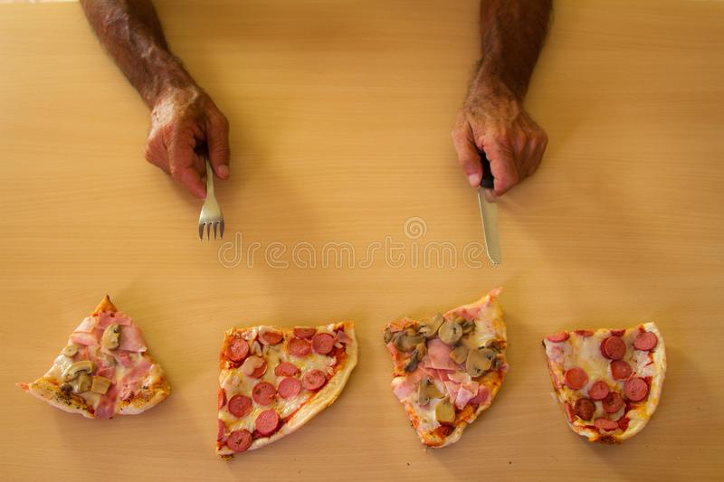 Italian pizza approaching the eater`s hands royalty free stock photo