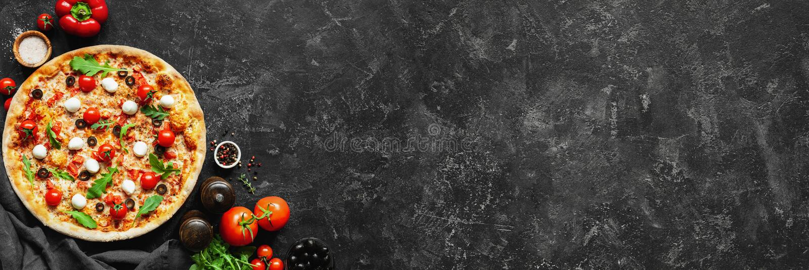 Italian pizza and pizza cooking ingredients on black concrete background royalty free stock photos