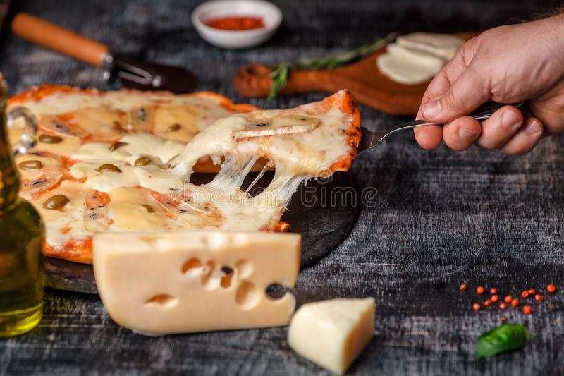 Italian pizza with different sorts of cheese on a stone and a black scratched chalk board. Italian traditional food royalty free stock photos