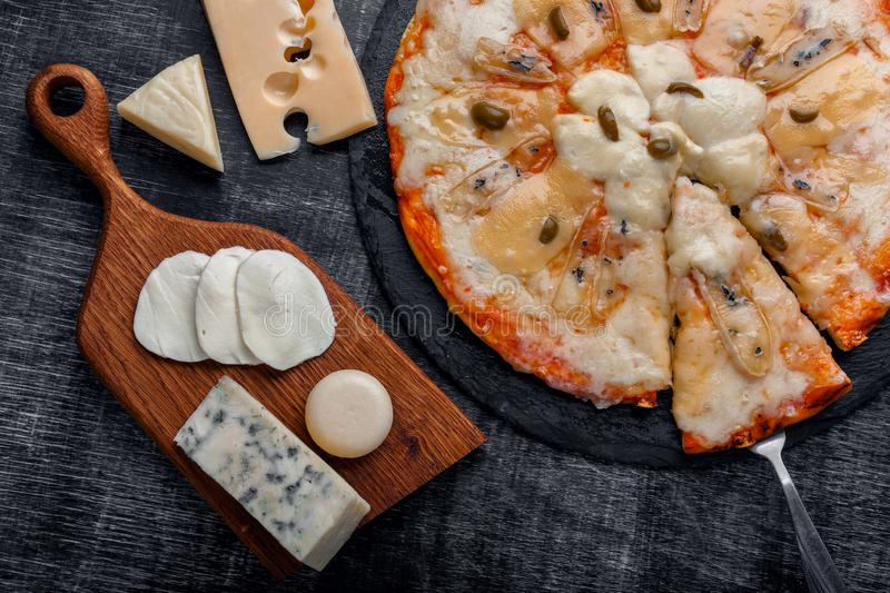 Italian pizza with different sorts of cheese on a stone and a black scratched chalk board. Italian traditional food royalty free stock image