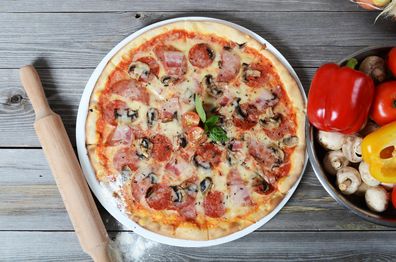 Italian pizza with a ham and mushrooms stock images