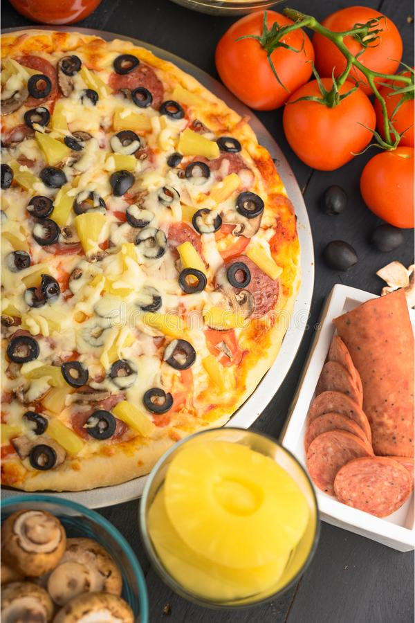 Italian pizza with ingredients on a dark background. Vertical photo.  royalty free stock images