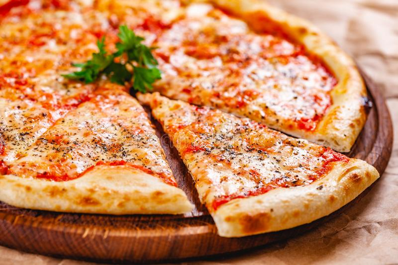 Italian Pizza Margherita with tomatoes and mozzarella cheese on wooden cutting board. Close up stock photos
