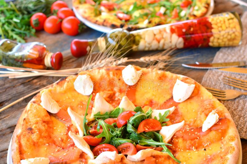 Italian pizza on a rustic cuisine with different ingredients. Italian pizza on a rustic cuisine with different ingredients royalty free stock photos