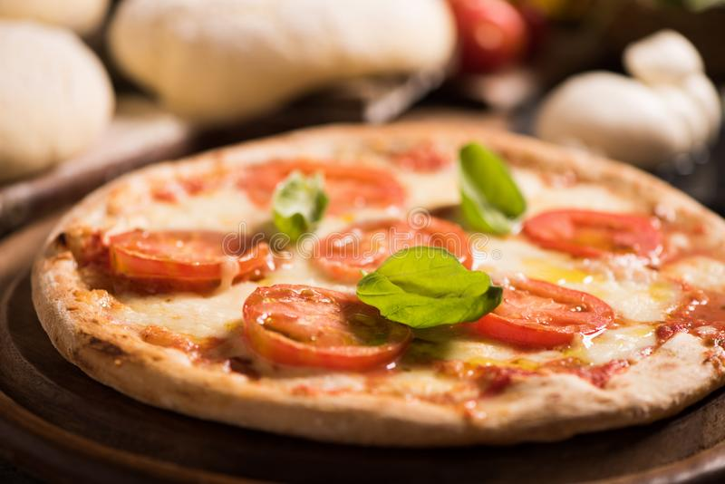 Italian pizza with tomato topped with melted golden mozzarella. Italian pizza with tomato topped with melted golden cheese mozzarella and basil served on a round stock photography