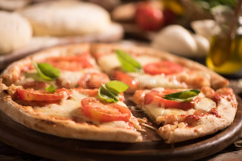Italian pizza with tomato topped with melted golden mozzarella. Italian pizza with tomato topped with melted golden cheese mozzarella and basil served on a round stock photos