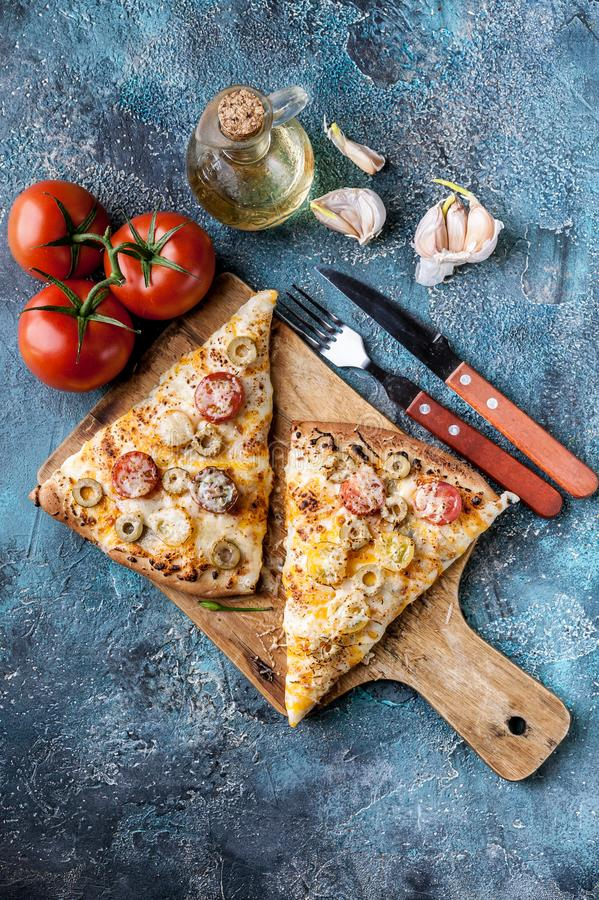 Italian pizza with tomatoes and mozzarella on a wooden cutting board. Vertical shot stock photos