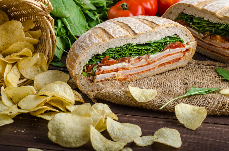 Italian Pressed Sandwich. Full of tasty. Italian ham and cheese, spinach, homemade chips side dish stock images