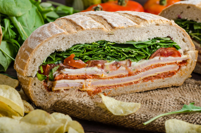 Italian Pressed Sandwich. Full of tasty. Italian ham and cheese, spinach, homemade chips side dish royalty free stock image