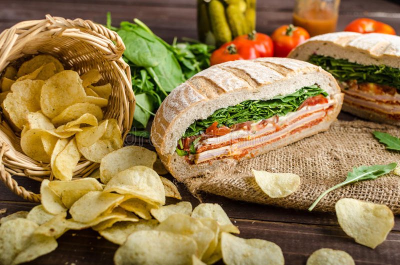Italian Pressed Sandwich. Full of tasty. Italian ham and cheese, spinach, homemade chips side dish royalty free stock images