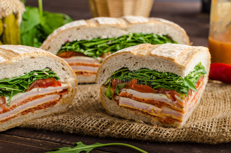 Italian Pressed Sandwich. Full of tasty. Italian ham and cheese, spinach, homemade chips side dish stock image