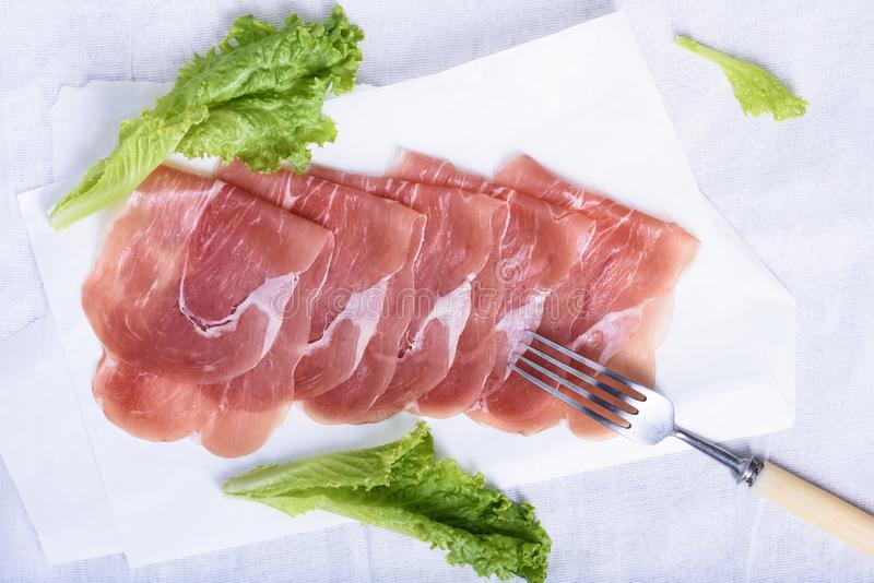 Italian prosciutto, Cured Pork Ham. Sliced meat snack. With salad. Above view stock images