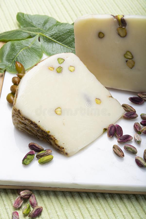 Italian provolone or provola cheese made in Sicily with tasty green Bronte pistachio nuts served on white marble plate close up. Cheese collection, Italian royalty free stock images
