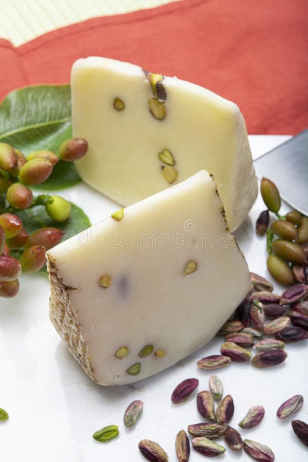 Italian provolone or provola cheese made in Sicily with tasty green Bronte pistachio nuts served on white marble plate close up. Cheese collection, Italian stock image