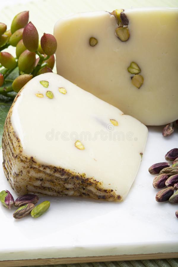 Italian provolone or provola cheese made in Sicily with tasty green Bronte pistachio nuts served on white marble plate close up. Cheese collection, Italian royalty free stock image