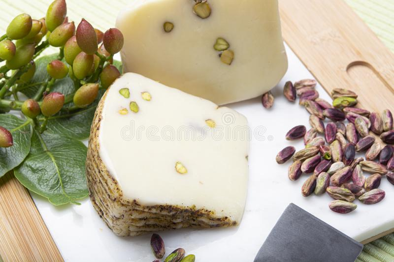 Italian provolone or provola cheese made in Sicily with tasty green Bronte pistachio nuts served on white marble plate close up. Cheese collection, Italian royalty free stock photography