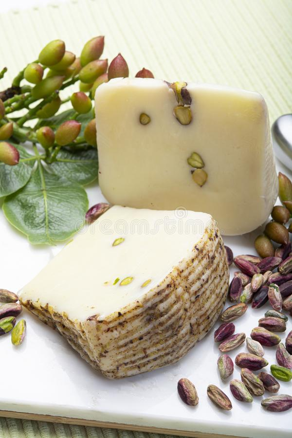 Italian provolone or provola cheese made in Sicily with tasty green Bronte pistachio nuts served on white marble plate close up. Cheese collection, Italian stock photography