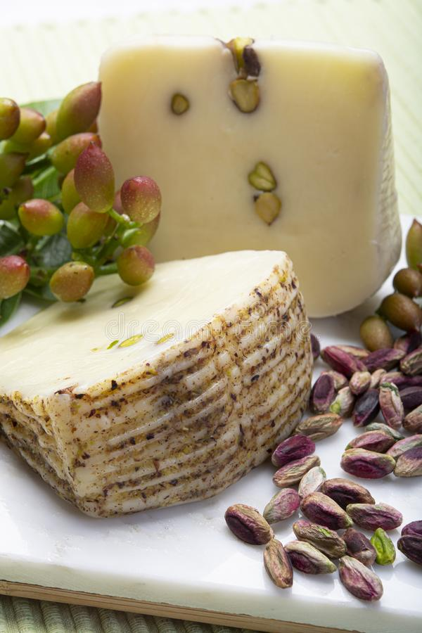 Italian provolone or provola cheese made in Sicily with tasty green Bronte pistachio nuts served on white marble plate close up. Cheese collection, Italian stock images