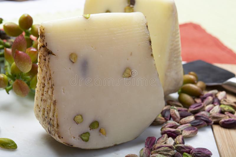 Italian provolone or provola cheese made in Sicily with tasty green Bronte pistachio nuts served on white marble plate close up. Cheese collection, Italian royalty free stock photo