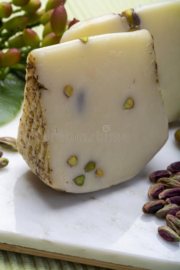 Italian provolone or provola cheese made in Sicily with tasty green Bronte pistachio nuts served on white marble plate close up royalty free stock image