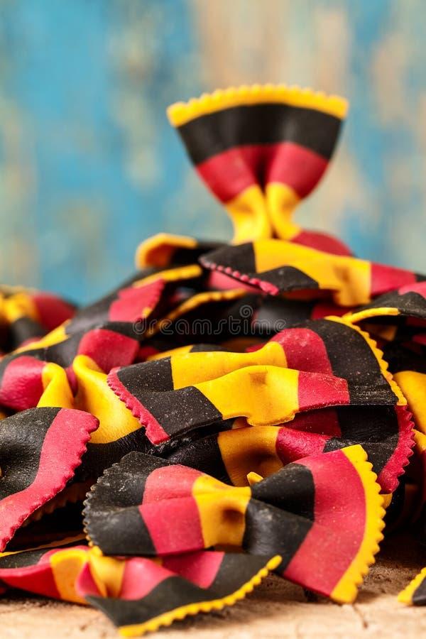 Italian raw multicolored farfalle pasta closeup on the table. royalty free stock photo