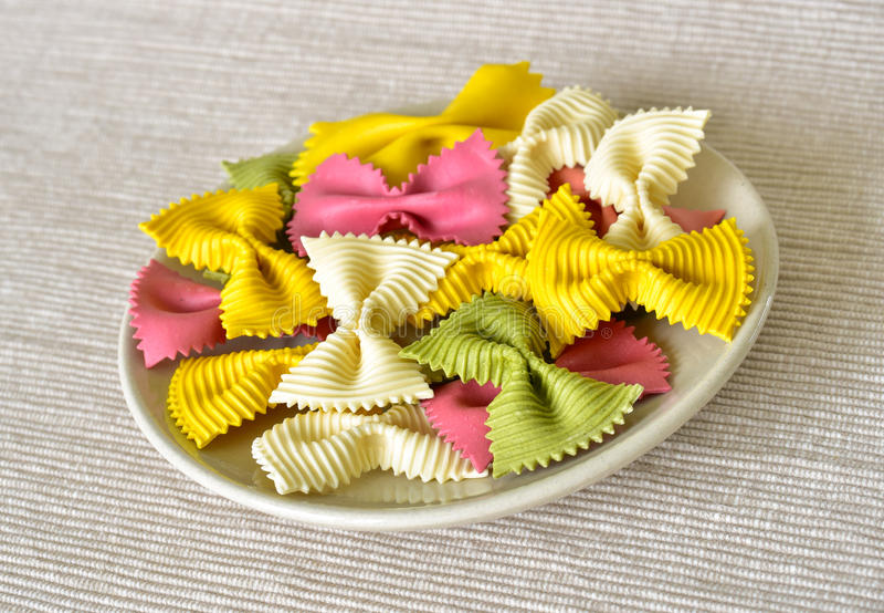 Italian raw pasta. Heap of Italian raw colorful ribbon shaped pasta on a plate, fabric background stock photos