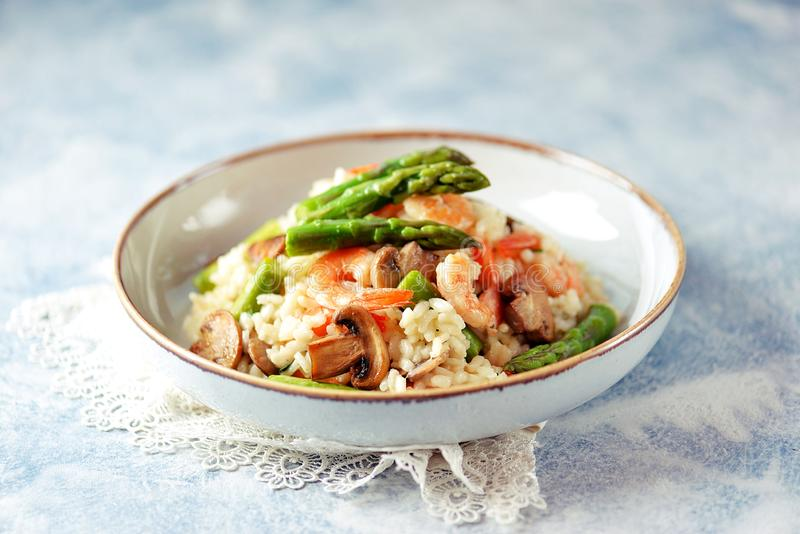 Italian risotto with shrimps, mushrooms, asparagus and parmesan. Healthy food. royalty free stock photography