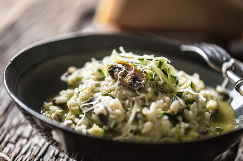 Italian risotto zucchini mushrooms and parmesan in dark plate royalty free stock photo