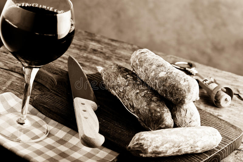 Italian salami and red wine. On wooden table royalty free stock image