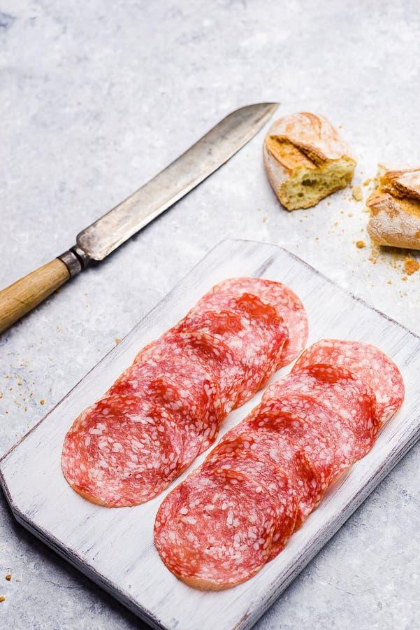 Italian salami on small cutting board on delicate background. Slices of italian salami on small cutting board on delicate background royalty free stock photos