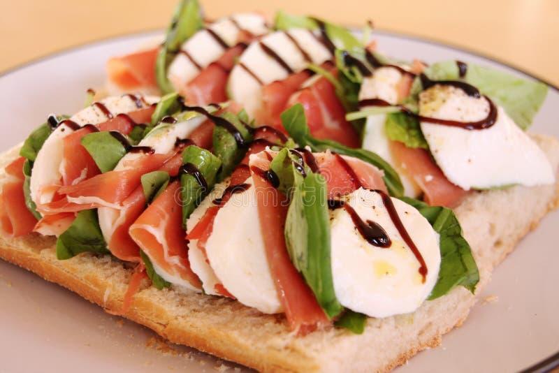 Italian sandwich. With mozzarella cheese, ham, fresh basil, pepper, olive oil and balsamico glaze stock image