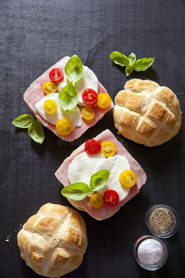 Italian sandwich with ham, Multicolored cherry tomatoes, basil. stock photo