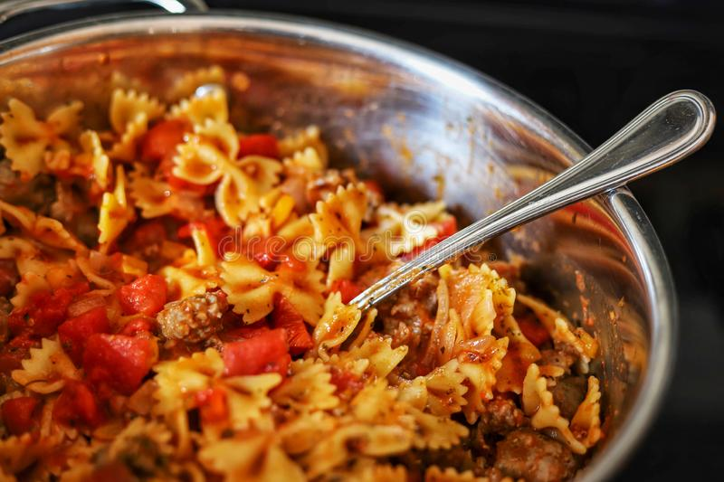 Italian sausage and peppers and bowtie pasta in a pan on the stove. Italian sausage, peppers and bowtie pasta in a pan on the stove royalty free stock photos